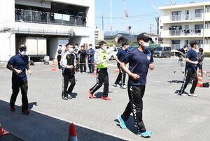 ビブスを着用した聖火ランナーを囲み、周囲の状況などを確認しながら走る県警の伴走部隊=佐賀市の県警機動隊