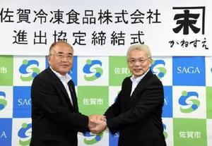 進出協定を結び、秀島市長(左)と握手する佐賀冷凍食品の古賀社長=佐賀市役所