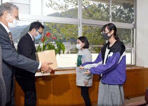 JAさがみどり地区茶業部会が、うがい用に配布するうれしの茶を受け取る児童=嬉野市の轟小学校