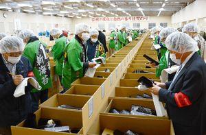 入札手板を片手に初摘みノリを品定めする商社の担当者=佐賀市の県有明海漁協