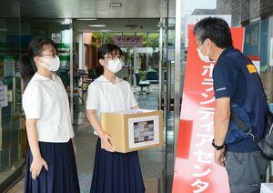 手縫いの雑巾を渡す鳥井なおさん(中央)と田中佑香さん(左)=大町町災害ボランティアセンター