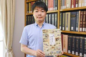 復刻した伝記絵本を手に「郷土学習に役立ててほしい」と話す三ツ松誠講師=佐賀市の佐賀大学