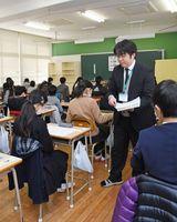 受験生に問題用紙を配る担当者=佐賀市の成穎中学校