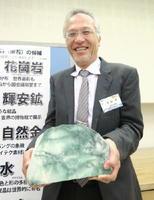 「日本の石」に選ばれた翡翠を持つ日本鉱物科学会の土山明会長=24日午後、金沢市の金沢大