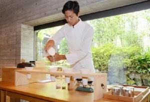 「茶師」として白い制服と洗練された所作で茶を入れる副島園の松田二郎さん=嬉野市の和多屋別荘