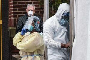 新型コロナウイルスが流行する米ニューヨークで、遺体安置所として使われるトラックの外に立つ医療関係者=3日(ゲッティ=共同)