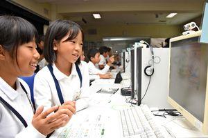 パソコン上で自動車生産と環境の関係について学ぶゲームに挑戦する児童たち=神埼市の西郷小