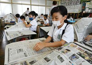 新聞の中からクイズの答えを探す児童たち=神埼市の千代田中部小