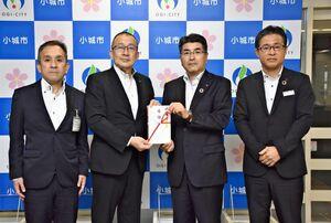 江里口秀次小城市長(左から2人目)に寄付金を手渡した中島信哉社長(同3人目)=市役所