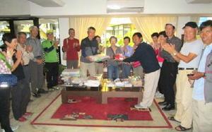 カトマンズ市内のホテルでネパール山岳協会理事のティカ・グルーンさん(前列中央)にパソコンを手渡す金立水曜登山会の石橋清志理事長