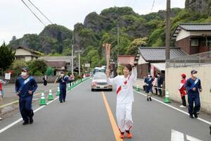 大分県中津市を走る聖火ランナー。奥は耶馬渓=23日午後(代表撮影)
