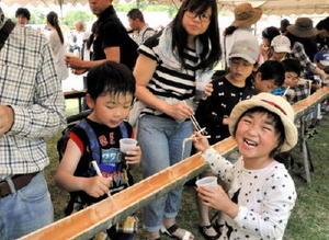 そうめん流しを楽しむ来場者たち=吉野ケ里歴史公園