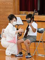 髙橋浩寿さんと一緒に津軽三味線の演奏に挑戦する児童=神埼市の神埼小