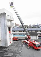 はしご車の配備式で救助訓練を披露する救急隊員=鳥栖市本町の鳥栖・三養基地区消防事務組合
