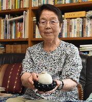 焼き物の手りゅう弾を手にする宮島トミエさん。終戦から約10年後、有田陶器市の処分品コーナーで見つけたという=伊万里市二里町の自宅