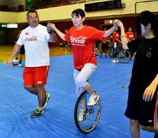 指導員らの手を支えに前に進む参加者=佐賀市の市村記念体育館