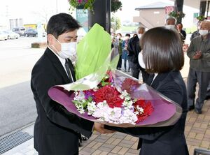 職員から花束を受け取る武広勇平氏=上峰町役場玄関前