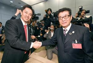 2025年万博の大阪開催が決まり、握手する松井一郎大阪府知事(右)と吉村洋文大阪市長=23日、パリ(共同)