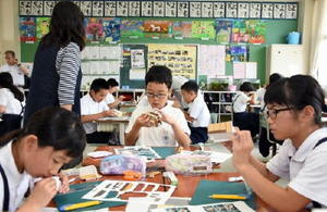 真剣な表情で折り紙キット模型の完成を目指す児童たち=鹿島市浜町の浜小学校