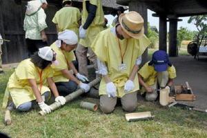 のこぎりやなたなどを使って竹から食器を作る参加者