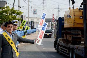 追突注意などのポップを掲げ、交通安全を呼び掛ける松尾佳昭町長(手前)ら=有田町役場前の国道202号沿い