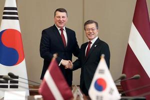 ラトビアのべーヨニス大統領(左)と握手を交わす韓国の文在寅大統領=13日、ソウル(韓国大統領府提供・共同)