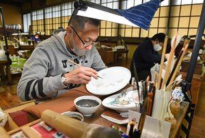 一筆一筆丁寧に絵付けする有田町の柿右衛門窯の職人。九州観光推進機構による米英豪での市場調査では、陶磁器の関心が最も高かった