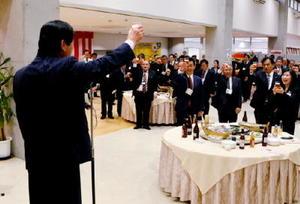 山本茂雄市議会議長(左)の発声で乾杯する出席者=多久市の「あいぱれっと」