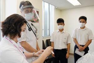 唐津商高ボランティア同好会から手作りのフェイスシールドを受け取った済生会唐津病院の関係者=唐津市の同病院