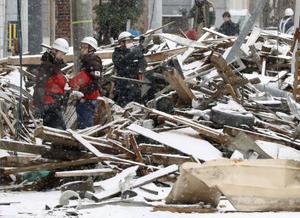 爆発のあった現場付近を調べる総務省消防庁の職員ら=18日午前、札幌市豊平区