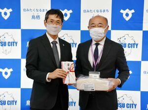 橋本康志市長(右)にウレタン製のマスクを贈った八巻一彦ブリヂストン鳥栖工場長=鳥栖市役所