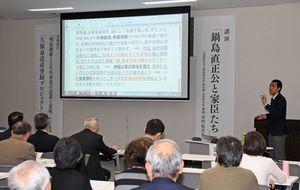 講演をする富田学芸員(右)=佐賀市の佐賀商工ビル
