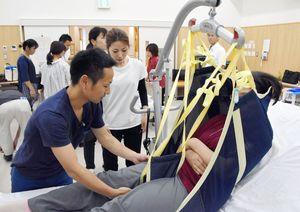 リフトを使った「抱え上げない介護」を実演する塚原さん(左)=佐賀市の県在宅生活サポートセンター