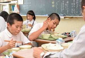 太良町産の鶏肉にかぶりつく児童=多良小学校