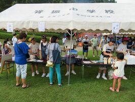 地元企業の商品に売値をつけ、祭りで販売する脊振中の生徒ら=8月、神埼市脊振町の高取山公園(学校提供)