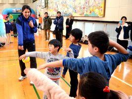 バレーボール元日本代表の迫田さおりさん(奥)からボールの打ち方を学ぶ子どもたち=吉野ヶ里町の東脊振小