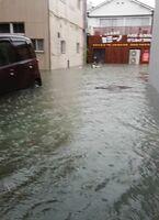 大雨で浸水したときの創作居酒屋カミーノ(奥)=8月28日午前7時半ごろ、佐賀市大財(同店提供)