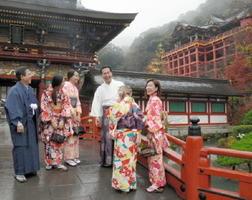 境内には、和装で散策を楽しむタイ人の姿もある。タイ語を学んでいる鍋島朝寿権宮司(中央)がもてなす=鹿島市の祐徳稲荷神社