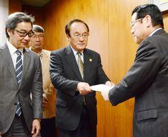 鹿島市民会館の計画見直し案をまとめ、樋口久俊市長に手渡す中村雄一郎座長(中央)=鹿島市役所