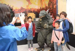 ゴジラと記念撮影する来場客=佐賀市の佐賀県立美術館