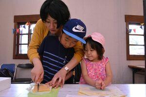 固まった「生キャラメル」を切る親子=佐賀市のどんぐり村