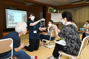 学生が見せる端末で、離れた場所にいる学生との交流を楽しむ住民=佐賀市の勧興公民館