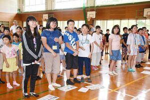 歓迎集会で西川登小の子どもたちと一緒に「ゴーゴーゴーたけおうむ」を歌う雄武町の小学生=西川登小体育館