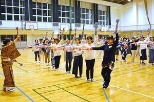 銭太鼓を持ち、踊りの練習をする4区踊り隊メンバー=有田中体育館