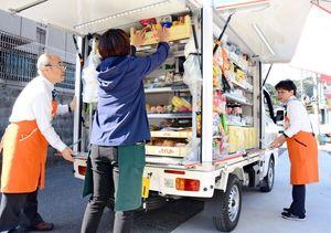 住宅地で移動スーパー「とくし丸」を止め、開店準備をするスタッフ=唐津市唐房