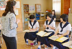 自分の名前の中国語読みを覚え、発音を講師にチェックしてもらう生徒=神埼市の脊振中