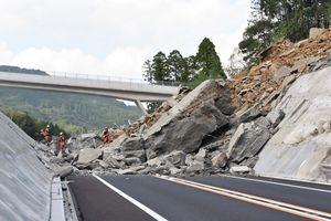西九州自動車道でのり面が崩落。巻き込まれた人がいないか調べる佐賀広域消防局の高度救助隊=10月1日、伊万里市南波多町