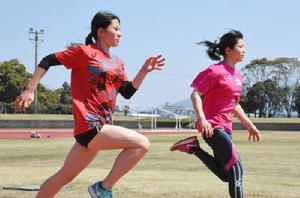 唐津東高3年生で、ともに県トップの短距離選手の本山陽菜さん(左)と智菜さん姉妹=唐津市陸上競技場