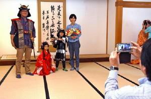 お姫様や武士の衣装を身に着けて記念撮影に臨む家族=佐賀市城内の佐賀城本丸歴史館