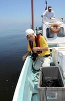 鹿島市沖の環境調査に取り組む佐賀大の速水祐一准教授。干潟や浅い海域を重点的に調べている=2015年8月、佐賀県鹿島市沖
